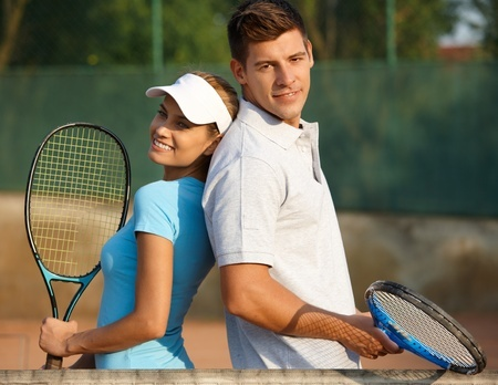 Man and Woman Posing with Tennis Rackets